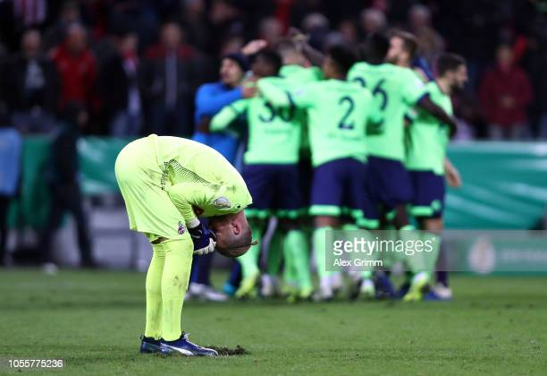 Timo Horn of 1.FC Koeln reacts as FC Schalke 04 players celebrate following victory in a penalty shoot out during the DFB Cup match between 1. FC...