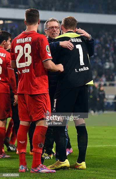 Timo Horn of Koeln celebrates with head coach Peter Stoeger after winning the DFB Cup second round match between MSV Duisburg and 1 FC Koeln at...