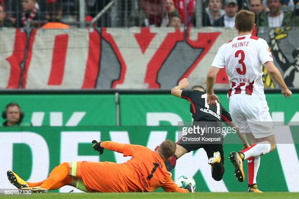 Timo Horn of Koeln fouls Mijat Gacinovic of Frankfurt which results in a penalty for Frankfurt during the Bundesliga match between 1. FC Koeln and...