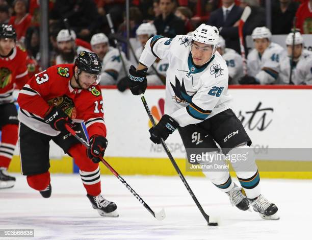 Timo Meier of the San Jose Sharks advances the puck chased by Tomas Jurco of the Chicago Blackhawks at the United Center on February 23 2018 in...