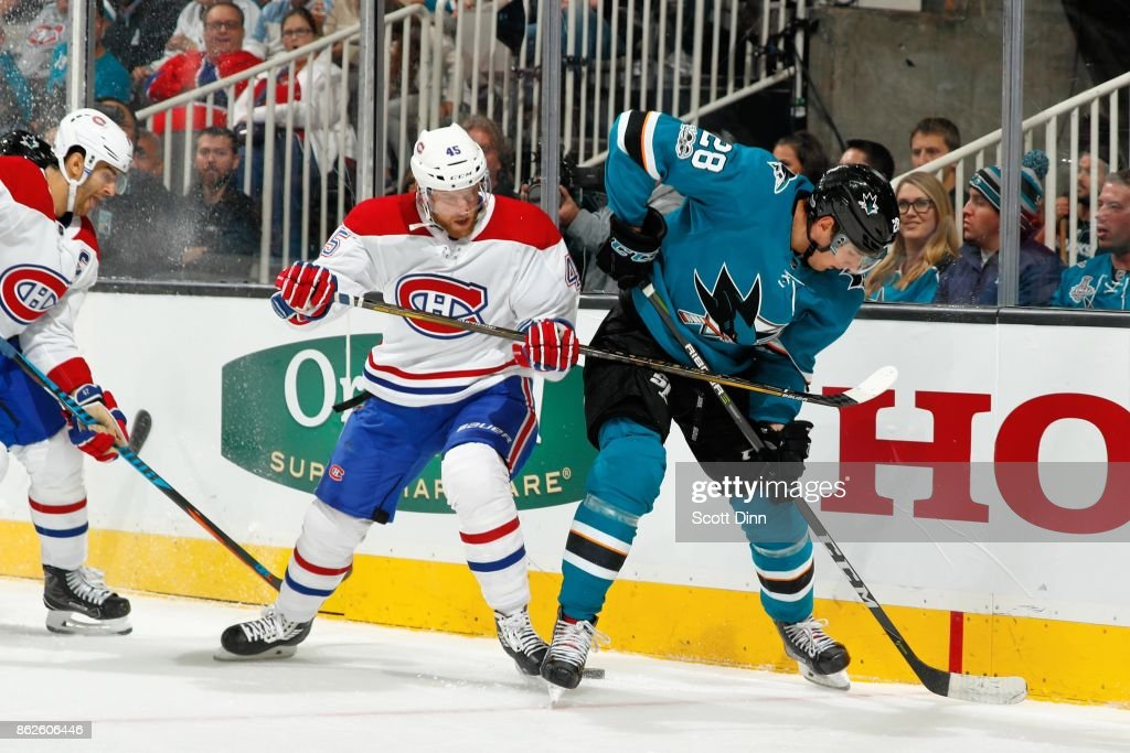 Timo Meier #28 of the San Jose Sharks and Joe Morrow #45 of the Montreal Canadiens battle for the puck along the boards at SAP Center on October 17, 2017 in San Jose, California.