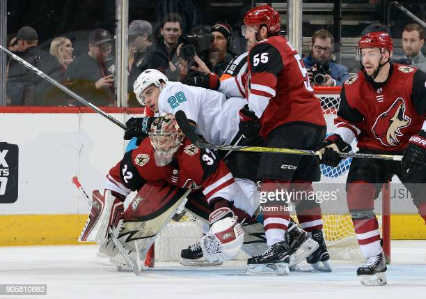 Timo Meier of the San Jose Sharks lands on goalie Antti Raanta of the Arizona Coyotes as he battles with Jason Demers of the Coyotes during the...
