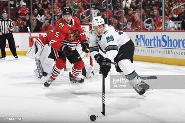 Timo Meier of the San Jose Sharks reaches for the puck ahead of Connor Murphy of the Chicago Blackhawks in the second period at the United Center on...