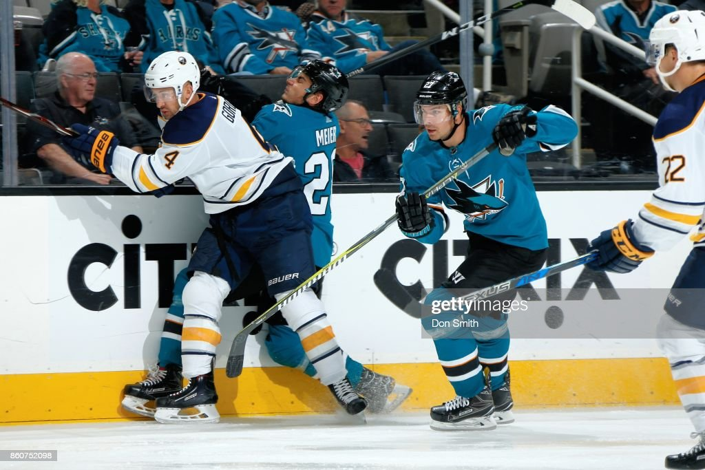 Timo Meier #28 of the San Jose Sharks takes a hit from Josh Gorges #4 of the Buffalo Sabres as Joonas Donskoi #27 of the San Jose Sharks chases the puck at SAP Center at San Jose on October 12, 2017 in San Jose, California.