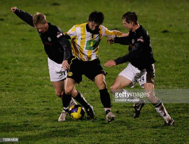 Timo Schulz and Carsten Rothenbach of Pauli tackle Denis Omerbegovic during the Third League match between Borussia Dortmund II and FC StPauli at the...