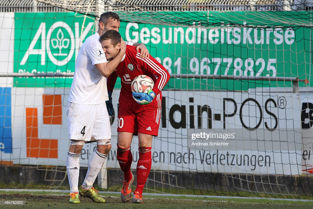 Timo Wenzel and Keeper Morten Jensen of Elversberg during the Regionalliga Suedwest match between SV Elversberg (white) and 1. FC Saarbruecken (blue) on February 28, 2015 in Neunkirchen, Germany.