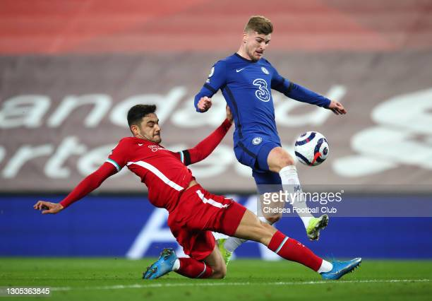 Timo Werner of Chelsea is challenged by Ozan Kabak of Liverpool as he scores his team's first goal during the Premier League match between Liverpool...