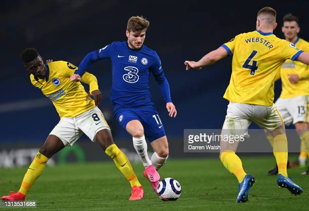 Timo Werner of Chelsea is put under pressure by Yves Bissouma and Adam Webster of Brighton & Hove Albion during the Premier League match between...