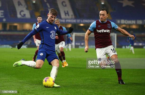 Timo Werner of Chelsea shoots under pressure from Mark Noble of West Ham United during the Premier League match between Chelsea and West Ham United...