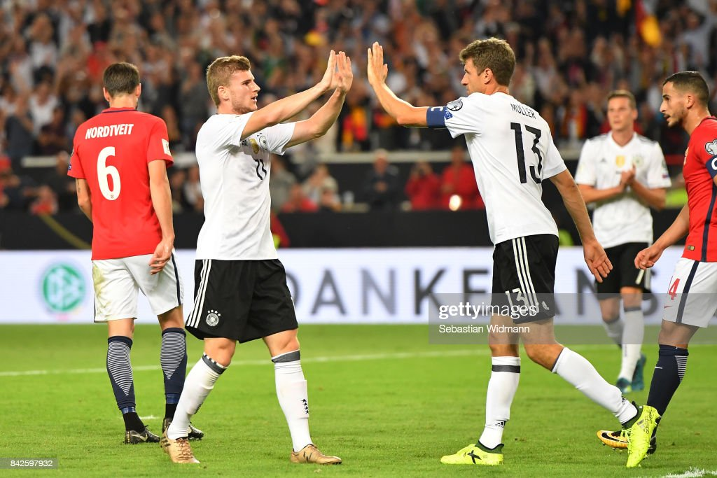 Timo Werner of Germany (l) is celebrated by Thomas Mueller of Germany after he scored to make it 3:0 during the FIFA 2018 World Cup Qualifier between Germany and Norway at Mercedes-Benz Arena on September 4, 2017 in Stuttgart, Baden-Wuerttemberg.