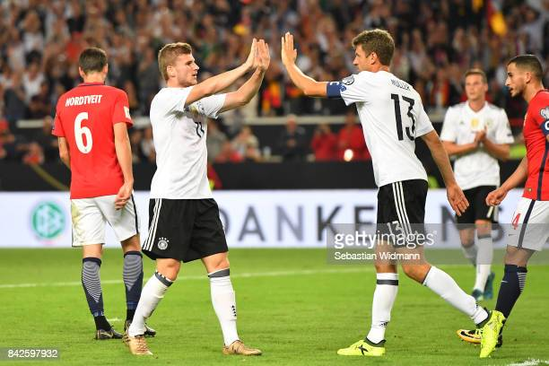 Timo Werner of Germany is celebrated by Thomas Mueller of Germany after he scored to make it 30 during the FIFA 2018 World Cup Qualifier between...