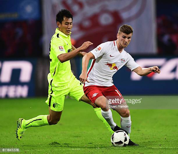 Timo Werner of Leipzig is challenged by DongWon Ji of Augsburg during the Bundesliga match between RB Leipzig and FC Augsburg at Red Bull Arena on...