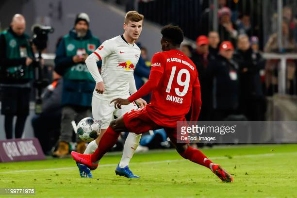 Timo Werner of RB Leipzig and Alphonso Davies of FC Bayern Muenchen battle for the ball during the Bundesliga match between FC Bayern Muenchen and RB...