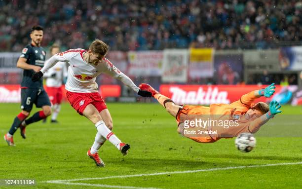 Timo Werner of RB Leipzig scores his team's third goal against goalkeeper Robin Zentner of Mainz 05 during the Bundesliga match between RB Leipzig...