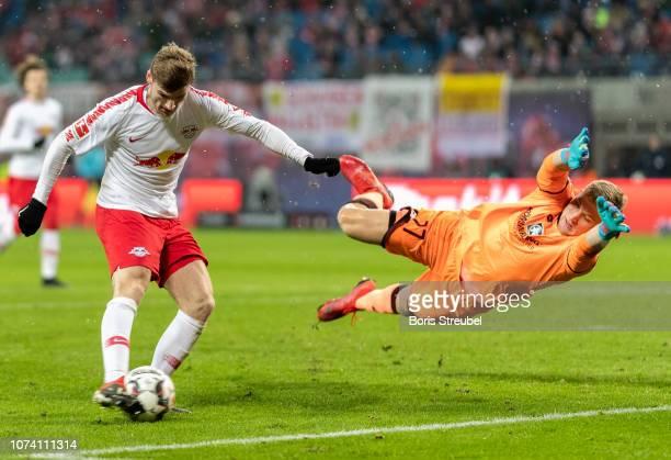 Timo Werner of RB Leipzig scores his team's third goal against goalkeeper Robin Zentner of Mainz 05 during the Bundesliga match between RB Leipzig...