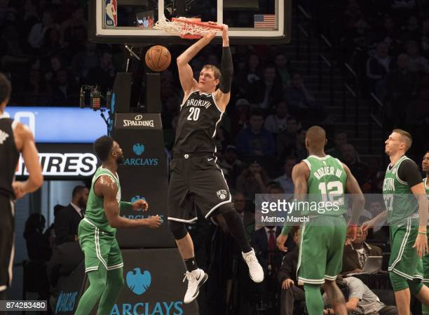 Timofey Mozgov of the Brooklyn Nets dunks the ball against Jaylen Brown and Terry Rozier III of the Boston Celtics during the first half of the NBA...