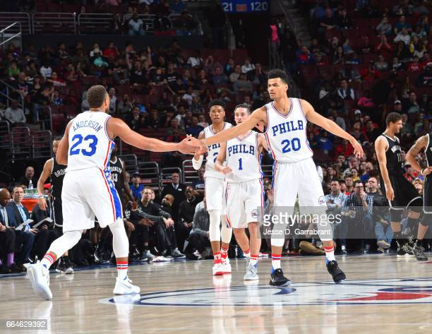Timothe LuwawuCabarrot and Justin Anderson of the Philadelphia 76ers shake hands against the Brooklyn Nets at Wells Fargo Center on April 4 2017 in...