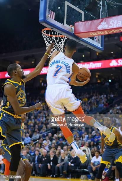 Timothe LuwawuCabarrot of the Oklahoma City Thunder goes in for a layup past Kevin Durant of the Golden State Warriors during an NBA basketball game...