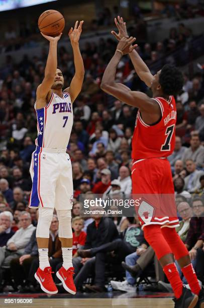Timothe LuwawuCabarrot of the Philadelphia 76ers shoots over Justin Holiday of the Chicago Bulls at the United Center on December 18 2017 in Chicago...
