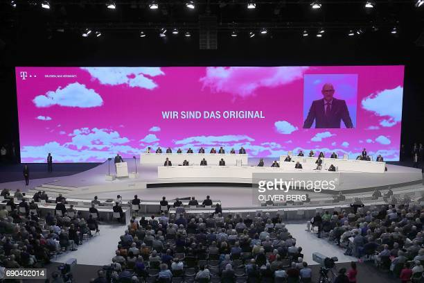 Timotheus Hoettges chairman of German telecommunications giant Deutsche Telekom is displayed on a giant screen as he speaks to the shareholders...