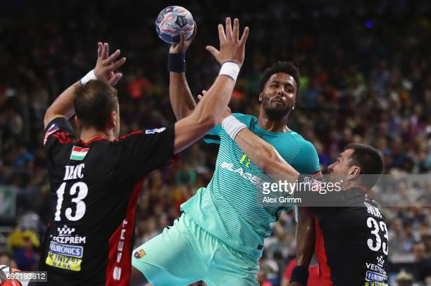 Timothey N'Guessan of Barcelona is challenged by Momir Ilic and Renato Sulic of Veszprem during the VELUX EHF FINAL4 3rd place match between Telekom...