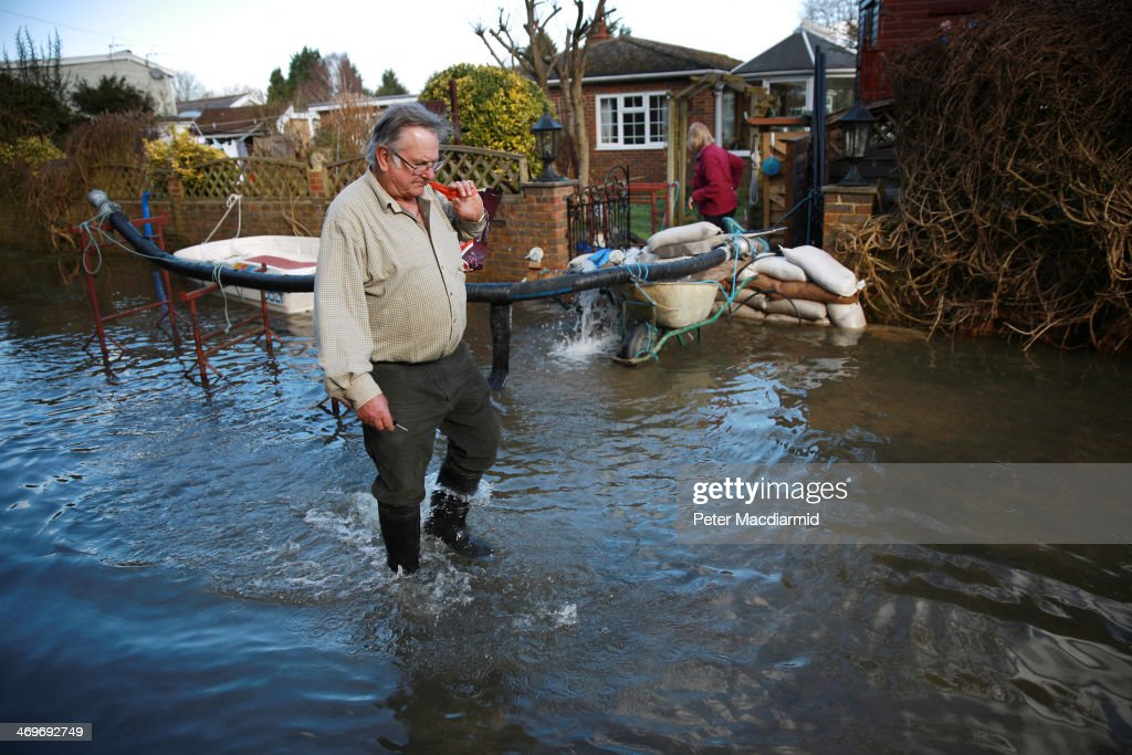Timothy Arrow leaves his property to go to the shops on February 16, 2014 in Chertsey, England. Mr Arrow's house has remained mostly free from flood water after he built a surrounding wall and constantly pumps out water from the nearby river Thames. Housing near the river Thames has suffered a week of flooding after the river burst it's banks on February 10, 2014.
