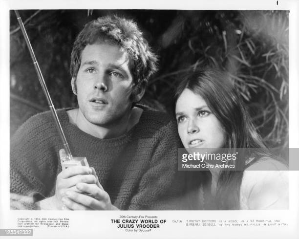 Timothy Bottoms and Barbara Seagull look up while holding electronic device in a scene from the film 'The Crazy World Of Julius Vrooder' 1974