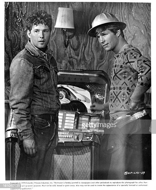 Timothy Bottoms and Jeff Bridges stand in front of a jukebox in a scene from the film 'The Last Picture Show' 1971