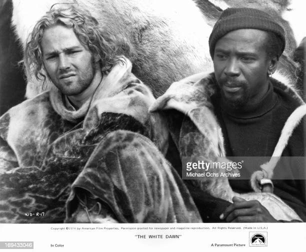 Timothy Bottoms and Louis Gossett Jr sitting together in a scene from the film 'The White Dawn' 1974