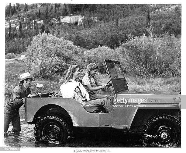 Timothy Bottoms pushes a jeep with Marilyn Hassett and Gretchen Corbett in a scene from the film 'The Other Side Of The Mountain Part II' 1978