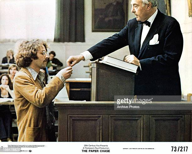 Timothy Bottoms standing below a podium receiving something that is being handed to him in a scene from the film 'The Paper Chase' 1973