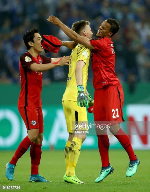 Timothy Chandler of Frankfurt celebrates victory with team mate Makoto Hasebe and Lukas Hradecky after the Bundesliga match between FC Schalke 04 and...