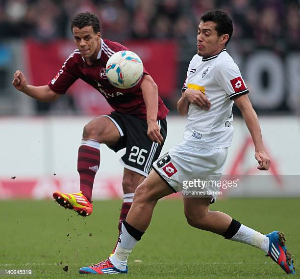 Timothy Chandler of Nuernberg battles for the ball with Juan Arango of Moenchengladbach during the Bundesliga match between 1FC Nuernberg and...