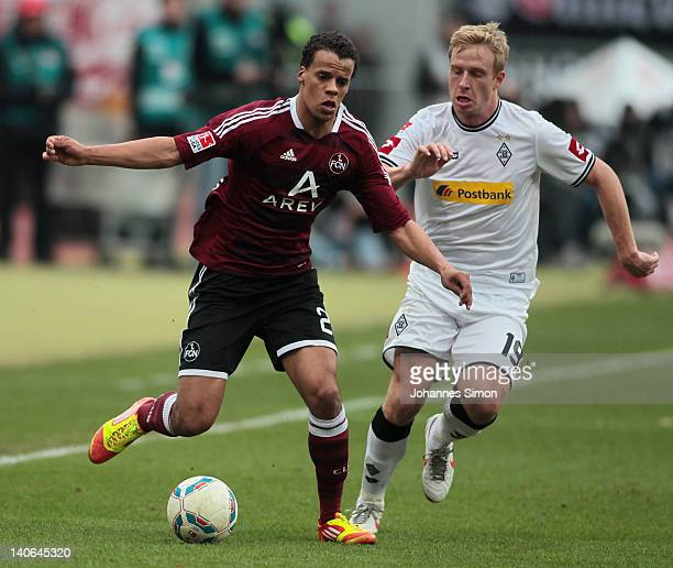 Timothy Chandler of Nuernberg battles for the ball with Mike Hanke of Moenchengladbach during the Bundesliga match between 1.FC Nuernberg and...