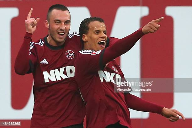 Timothy Chandler of Nuernberg celebrates scoring the opening goal with his team mate Josip Drmic during the Bundesliga match between 1. FC Nuernberg...