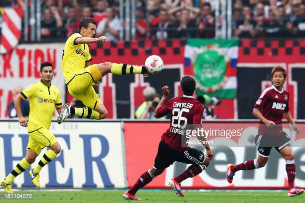 Timothy Chandler of Nuernberg is challenged by Ivan Perisic of Dortmund during the Bundesliga match between 1. FC Nuernberg and Borussia Dortmund at...