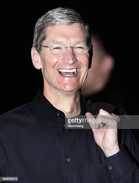 Timothy Cook, left, chief operating officer of Apple Inc., smiles during the keynote address at the MacWorld conference in San Francisco, California,...