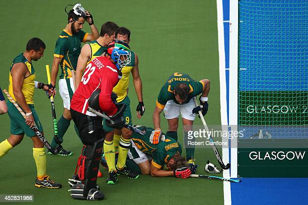 Timothy Drummond of South Africa is checked by team mates after he was struck on the head by the ball during the Men's preliminaries match between...