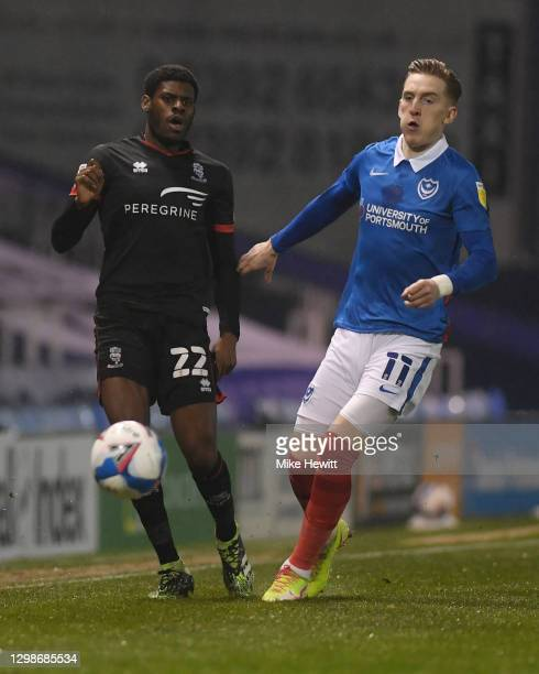 Timothy Eyoma of Lincoln City battles for possession with Ronan Curtis of Portsmouth FC during the Sky Bet League One match between Portsmouth and...
