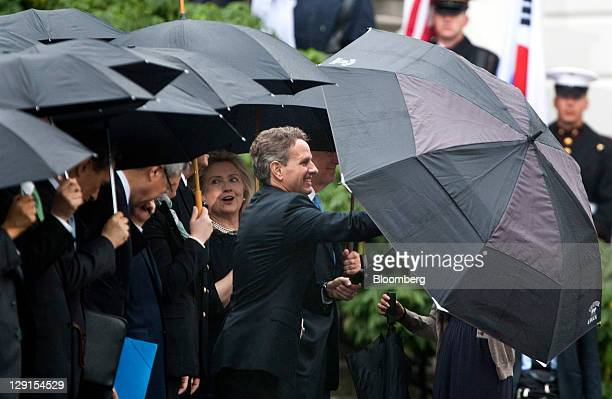 Timothy F Geithner US treasury secretary right opens an umbrella as Hillary Clinton US secretary of state second right comments before the State...