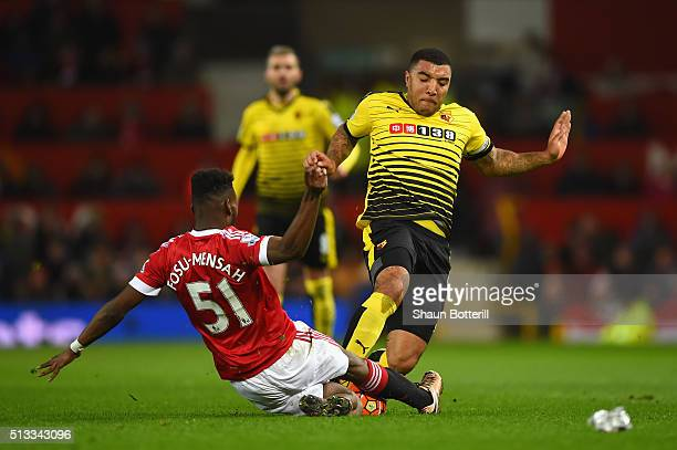 Timothy FosuMensah and Troy Deeney of Watford slide in to a challenge during the Barclays Premier League match between Manchester United and Watford...