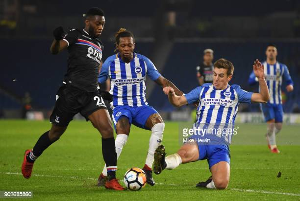 Timothy FosuMensah of Crystal Paalce is foiled by Uwe Huenemeier and Gaetan Bong of Brighton and Hove Albion during The Emirates FA Cup Third Round...