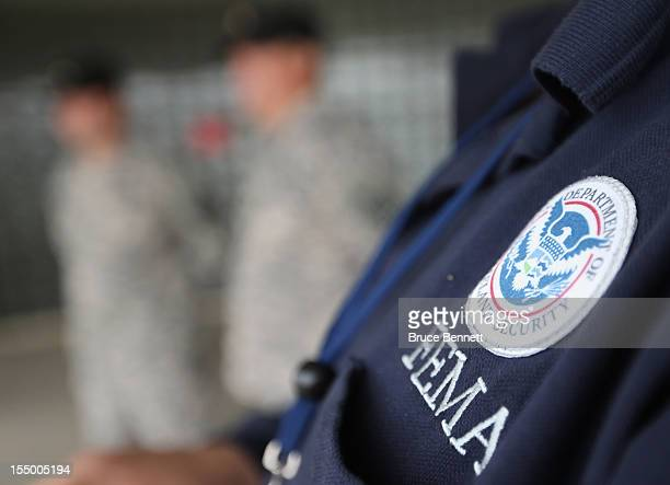 Timothy Henggeler, Logistics Specialist with FEMA speaks with New York guard members at Republic Airport in the aftermath of Hurricane Sandy on...
