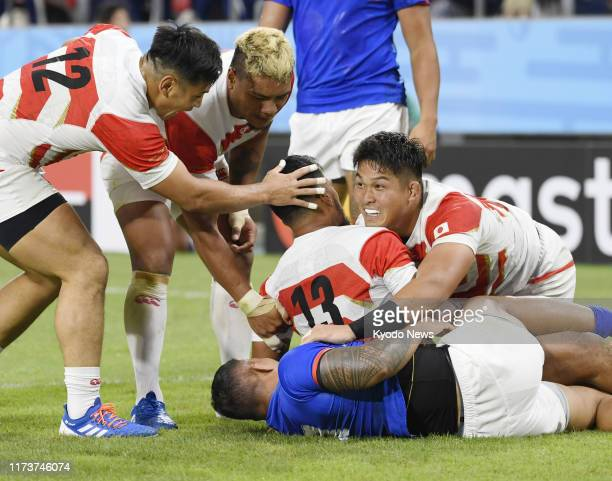 Timothy Lafaele of Japan is congratulated by teammate Kazuki Himeno after he scored a try during the first half of a Rugby World Cup Pool A match...