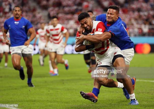 Timothy Lafaele of Japan is tackled by Alapati Leiua of Samoa as he goes on to score his team's first try during the Rugby World Cup 2019 Group A...