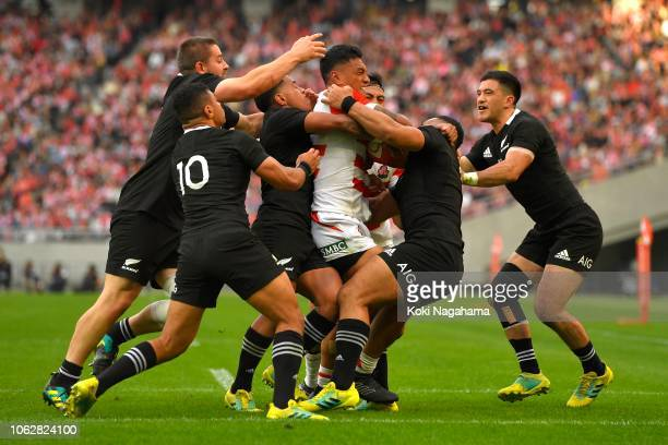 Timothy Lafaele of Japan is tackled by the All Blacks players during the test match between Japan and New Zealand All Blacks at Tokyo Stadium on...