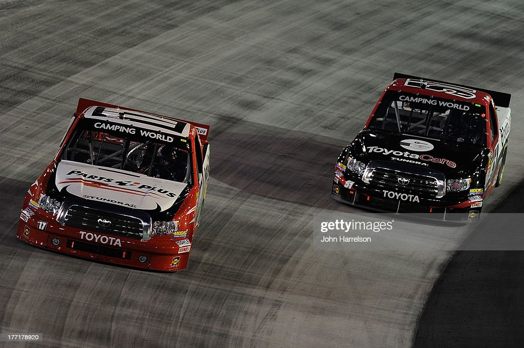 Timothy Peters, driver of the #17 Parts Plus Toyota, races with Kyle Busch, driver of the #51 ToyotaCare Toyota during the Camping World Truck Series UNOH 200 at Bristol Motor Speedway on August 21, 2013 in Bristol, Tennessee.