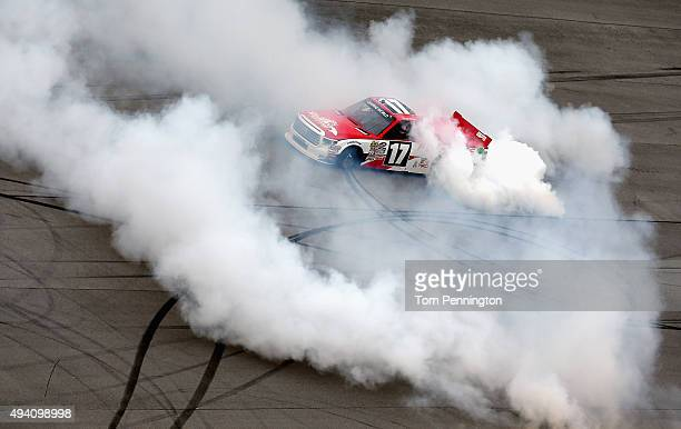 Timothy Peters driver of the Red Horse Racing Toyota celebrates with a burnout after winning the NASCAR Camping World Truck Series fred's 250 at...