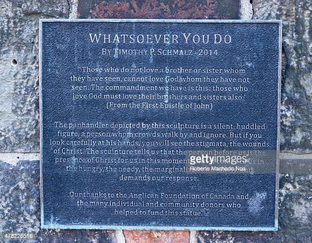 ITALY TORONTO ONTARIO CANADA Timothy Schmalz's Whatsoever You Do marker plaque mounted on grey brick wall in a Little Italy church
