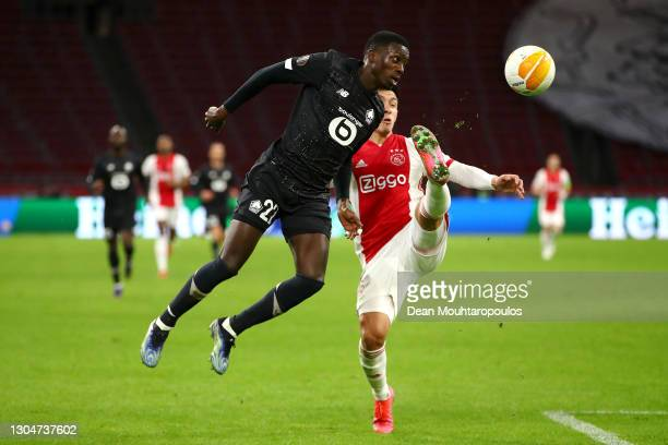 Timothy Weah of Lille battles for the ball with Lisandro Martinez of Ajax during the UEFA Europa League Round of 32 match between AFC Ajax and Lille...